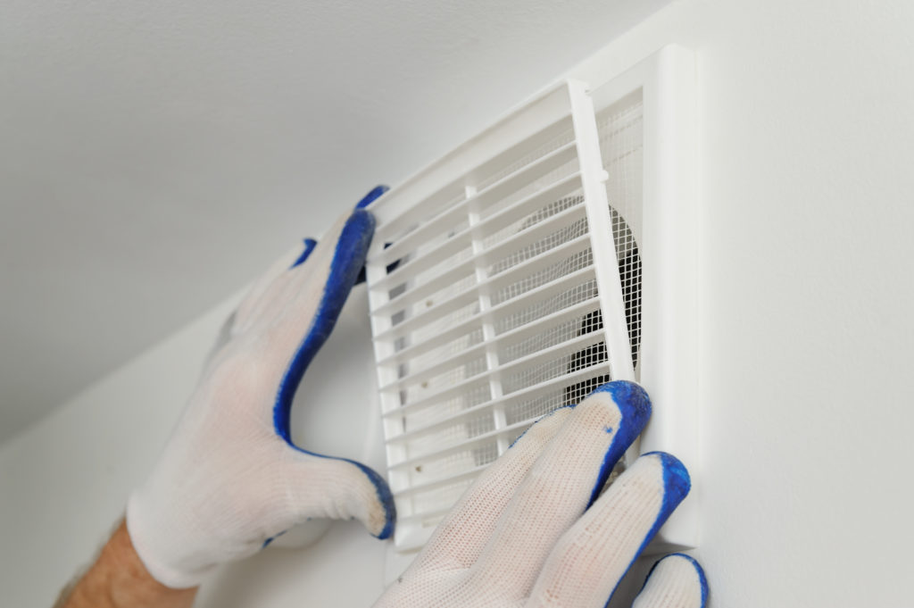 Worker installs ventilation grille on the wall.